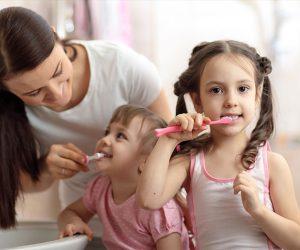 Niñas siguen consejos para lavarse bien los dientes.