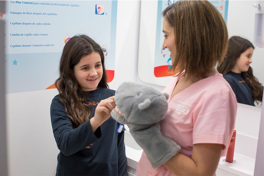 Enfermera del equipo Raga explica a una niña los beneficios de los tratamientos de ortodoncia en niños en ValenciaOrtodoncia Valencia ex